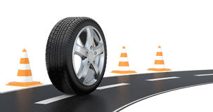 Automobile tire, road cone,  and long road Royalty Free Stock Photography
