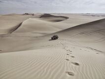 Automobile and Tire Tracks in a White Desert with Sand Dunes Stock Photography