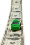 Automobile verde del giocattolo sulla strada dei soldi su fondo bianco Immagini Stock