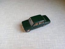 Automobile verde scuro di modello su un fondo grigio Fotografia Stock