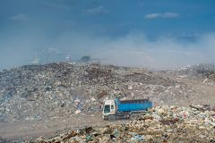 Automobile wagon at the huge garbage dump full of smoke, litter, plastic bottles,rubbish and trash at tropical island Royalty Free Stock Photo