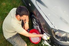 Automobile washing Equipaggi la pulizia della sua automobile facendo uso della spugna e spumi vista superiore fotografia stock libera da diritti