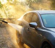 Automobile washing Automobile grigia di pulizia di colore facendo uso di acqua ad alta pressione i Fotografie Stock Libere da Diritti