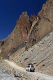 Automobile 4WD sulla strada non asfaltata accanto all'alta montagna della roccia, India del Nord Immagini Stock
