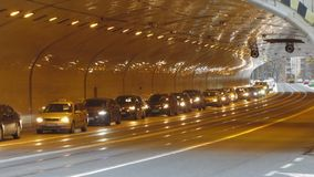 Automobiles driving with caution into tunnel equipped with new lights, traffic. Stock footage stock footage