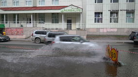 Automobiles driving on road over deep puddle and splashing water from wheels. PETROPAVLOVSK KAMCHATSKY CITY, KAMCHATKA PENINSULA, RUSSIAN FAR EAST - 12 MAY, 2018 stock video footage