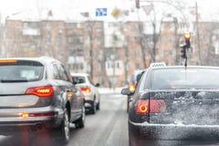 Automobili che stanno nella fila in ingorgo stradale sulla via della città sulla strada nevosa sdrucciolevole nell'inverno I veic Immagini Stock Libere da Diritti