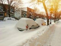 Automobili coperte di neve sulla via di inverno nel tramonto Immagini Stock