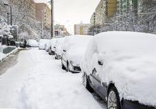 Automobili coperte parzialmente in neve Immagini Stock