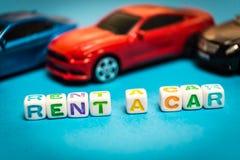 Automobili del giocattolo della foto L'iscrizione per affittare un'automobile fotografie stock