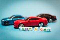 Automobili del giocattolo della foto L'iscrizione per affittare un'automobile immagini stock libere da diritti
