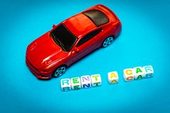 Automobili del giocattolo della foto L'iscrizione per affittare un'automobile fotografia stock libera da diritti