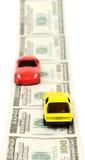 Automobili del giocattolo sopra molte fatture del dollaro Immagini Stock