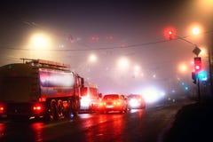 Automobili della città della nebbia di notte rosse Fotografia Stock
