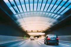 Automobili di accelerazione dentro un tunnel urbano della strada principale fotografia stock