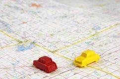 Automobili di plastica miniatura su una mappa Immagine Stock