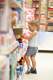 Automobili di sorveglianza del ragazzo nel negozio del giocattolo Fotografia Stock