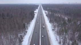 Automobili e camion che guidano sulla strada principale di inverno con la vista aerea nevosa della foresta archivi video