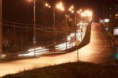 Automobili e l'altro azionamento trasporto sulla strada principale nella città di notte immagine stock