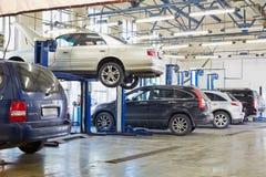 Automobili e sollevatori in officina del distributore di benzina Fotografia Stock Libera da Diritti