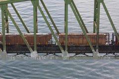Automobili ferroviarie che attraversano ponte ferroviario sopra acqua Fotografia Stock