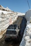 Automobili fuori strada Toyota che guida sulla strada della montagna in tunnel della neve circondato dagli alti cumuli di neve Fotografia Stock