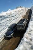 Automobili fuori strada Toyota e Mitsubishi che guidano sulla strada della montagna in tunnel della neve circondato dagli alti cu Immagine Stock