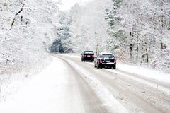 Automobili su una strada bianca di inverno immagine stock