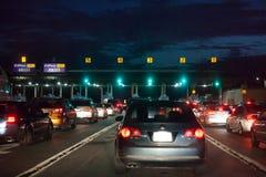 Automobili in un allineamento alla notte al casello da pagare la tassa del tributo immagine stock libera da diritti