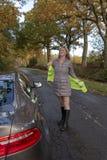 Automobilist die op een weerspiegelend jasje bij de kant van de weg zetten royalty-vrije stock fotografie