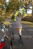 Automobilist die op een weerspiegelend jasje bij de kant van de weg zetten stock afbeeldingen