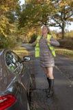 Automobilist die op een weerspiegelend jasje bij de kant van de weg zetten stock afbeelding