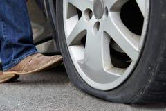 Automobiliste donnant un coup de pied le pneu plat sur la voiture photographie stock