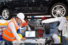 Automobilowy inżynier z pomocy inspec mechanicznym nowożytnym samochodem zdjęcia royalty free