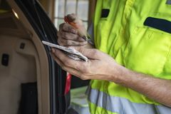 Automobilowy repairman stoi bezczynnie z powrotem samochód z hatchback z brudnymi rękami robi notatkom otwarte w małym notatniku  obrazy stock