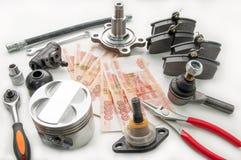 Automobilteile und Geld Stockfotos