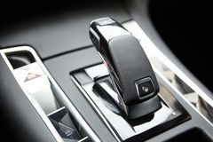 Automotive detail in a luxury car. Modern Luxury car inside. Interior of prestige modern car. Automatic gear stick shift.  royalty free stock images
