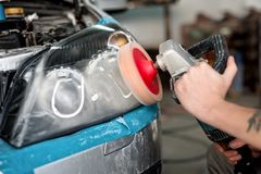 Automotive engineer polishing the headlight of a car Royalty Free Stock Image