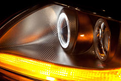 Automotive halogen headlight on sports car. Automotive halogen headlight from a sports car turned on; blinker, and parking light structure also displayed stock photo