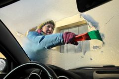 Automotive, ice cleaning from windshield. Winter scene, adult woman scraping ice from windshield of car Stock Photography