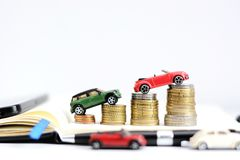 Automotive industry evolution concept with colored toy cars on pile of coins. Automotive industry evolution concept with colored toy cars on pile of money Royalty Free Stock Images