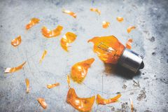 Damaged Light Bulb and Glass Shards. Automotive light bulb in broken condition and sharp glass shards scattered around it on textured background royalty free stock images