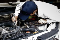 Automotive mechanic in uniform with wrench diagnosing engine under hood of car at the repair garage. Automotive mechanic in uniform with wrench diagnosing Stock Photo
