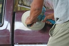 Automotive paint technician using grinder machine with wax on side of pickup , A part of the procedure to make a new color car. Close up Automotive paint stock photo