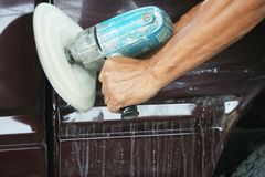 Automotive paint technician using grinder machine with wax on side of pickup , A part of the procedure to make a new color car. Close up Automotive paint royalty free stock photo