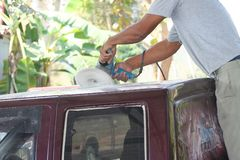 Automotive paint technician using grinder machine with wax on the top of pickup , A part of the procedure to make a new color car. Close up Automotive paint royalty free stock photo