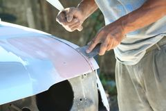 Automotive paint technician using paint on putty knife at bonnet , A part of the procedure to paint a new bonnet. Close up Automotive paint technician using stock image