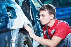 Automotive repair. mechanic puttying car body Royalty Free Stock Photo