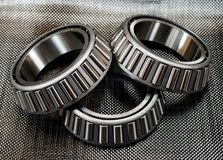 3 automotive tapered roller bearings on carbon fiber. 3 antique automotive tapered roller bearings on plain weave carbon fiber Stock Images