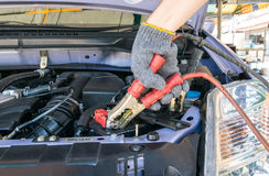 Automotive technician charging vehicle battery Stock Images